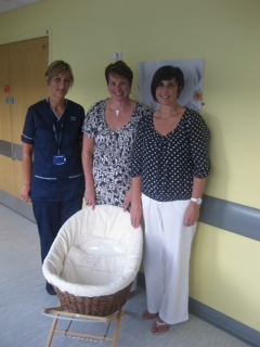 Picture shows Susan and Alison handing over the Moses basket and cold mat to Fiona Dodds,  Team Leader Midwife.